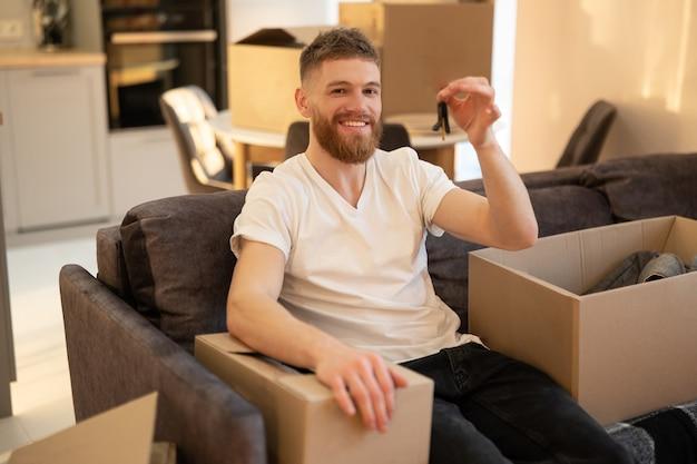Молодой человек сидит на диване и показывает ключ от нового дома. улыбающийся европейский бородатый парень, глядя на камеру. картонные коробки с вещами. концепция переезда в новую квартиру. интерьер однокомнатной квартиры