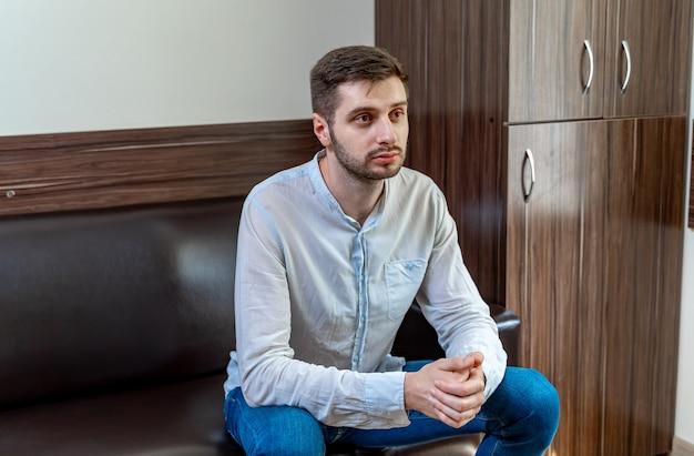 사무실의 응접실에서 소파에 앉아 있는 젊은 남자.