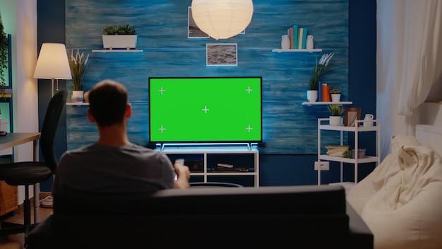 Tv에 녹색 화면이 있는 소파에 앉아 있는 젊은 남자