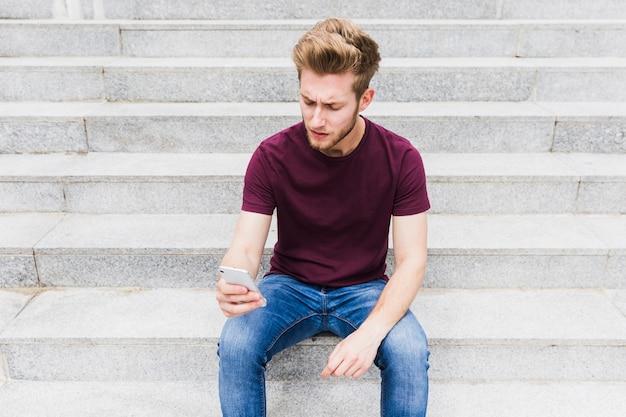 携帯電話を持って階段に座っている若い男