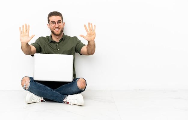 指で 10 を数える床に座っている若い男