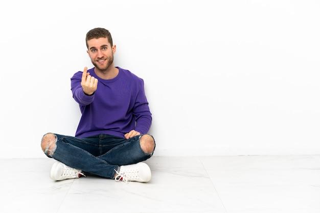 Молодой человек сидит на полу и делает жест