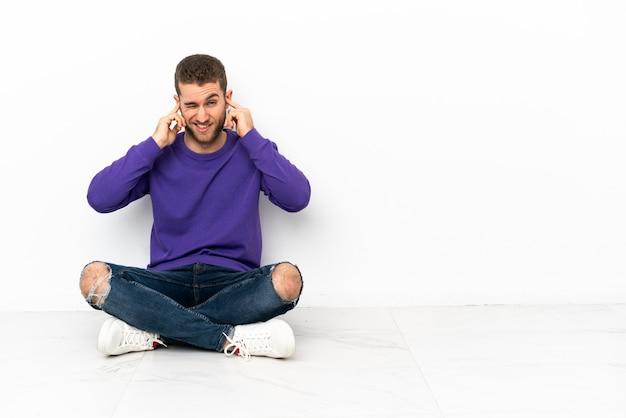 イライラして耳をふさいで床に座っている若い男