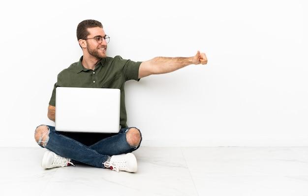 親指を立てるジェスチャーを与える床に座っている若い男