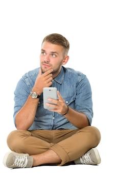 Молодой человек сидит на полу, воображая, держа смартфон