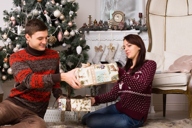 彼のガールフレンドに愛情のこもった笑顔でクリスマスプレゼントを与えるクリスマスツリーの前のリビングルームの床に座っている若い男