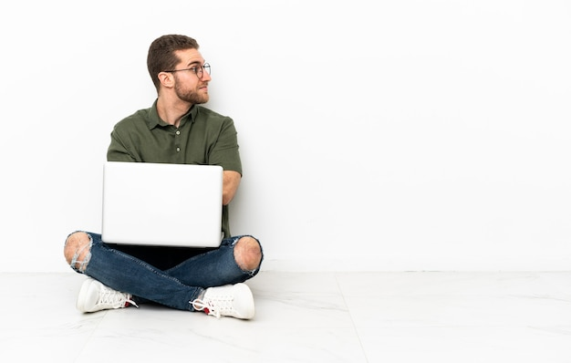 Молодой человек сидит на полу, скрестив руки
