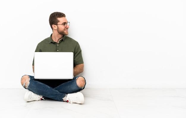 Молодой человек сидит на полу смотрит сбоку