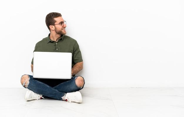 Молодой человек сидит на полу, смотрит в сторону и улыбается