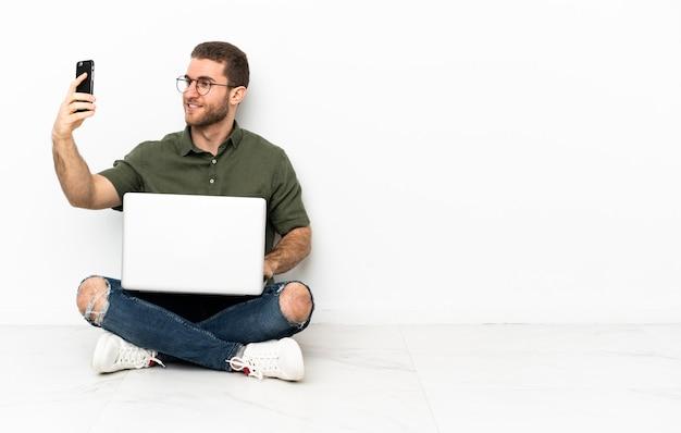Молодой человек сидит на полу, делая селфи