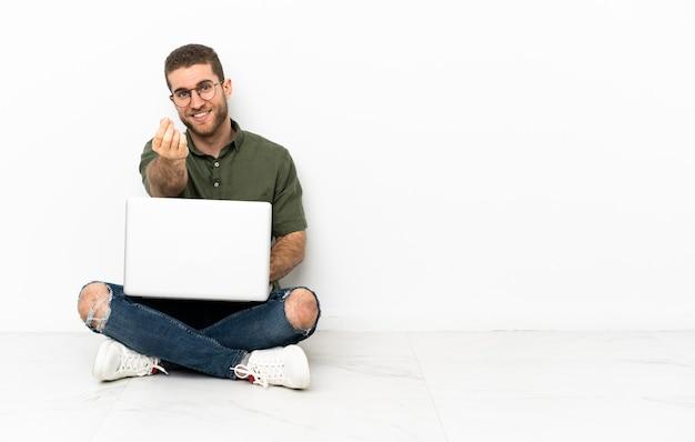 Молодой человек сидит на полу, делая денежный жест