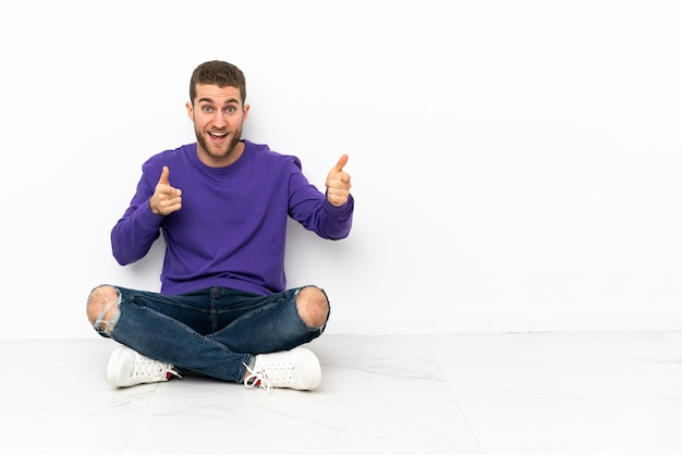 床に座って正面を向いて笑っている若い男