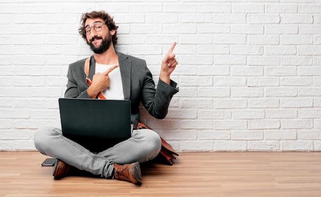Молодой человек, сидя на полу, улыбаясь и указывая