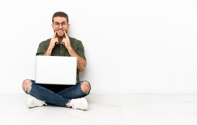 Молодой человек сидит на полу, улыбаясь счастливым и приятным выражением лица