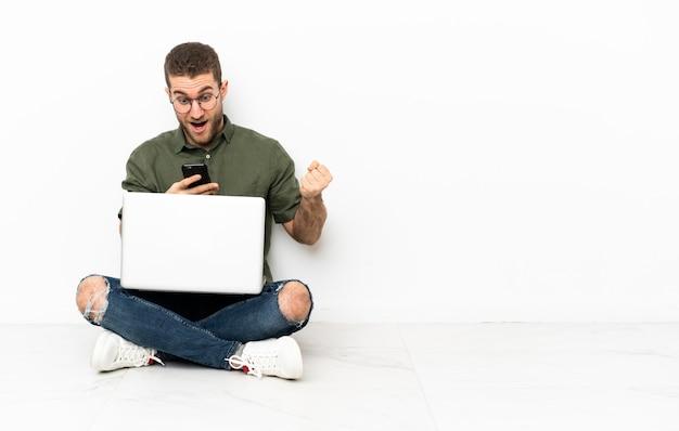 바닥에 앉아 놀라며 메시지를 보내는 청년