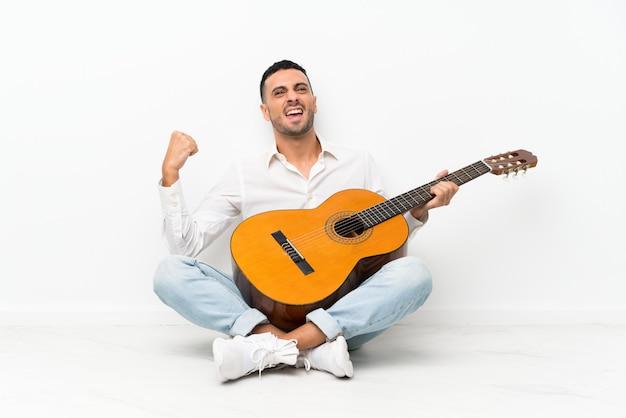 Молодой человек сидит на полу с гитарой празднует победу