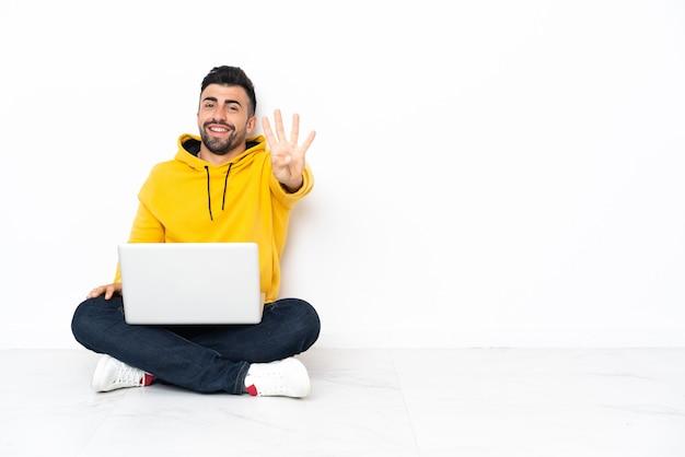 Молодой человек сидит на полу со своим ноутбуком счастливым и считает четыре пальцами