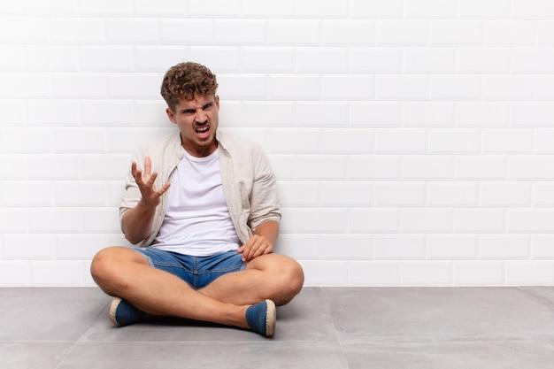 床に座っている若い男