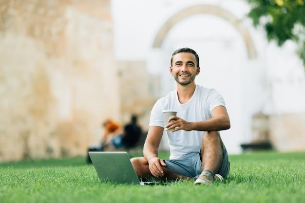 Молодой человек сидит на земле и работает над ноутбуком, пьет кофе в парке