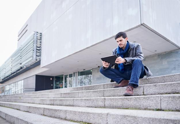 Молодой человек сидит на внешней лестнице публичной библиотеки, используя свой планшетный компьютер