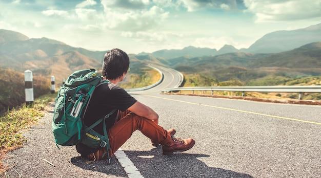 道端に座っている若い男。バックパッカー、旅行、休日の概念。