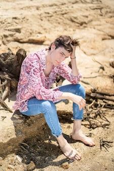 固定された外観のジーンズと花のシャツと砂の上に座っている若い男