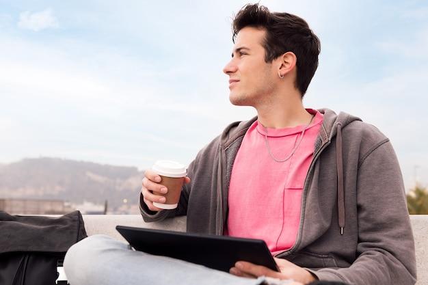 기술 및 도시 생활 방식의 태블릿 개념을 사용하여 야외에서 커피와 함께 앉아 있는 젊은 남자