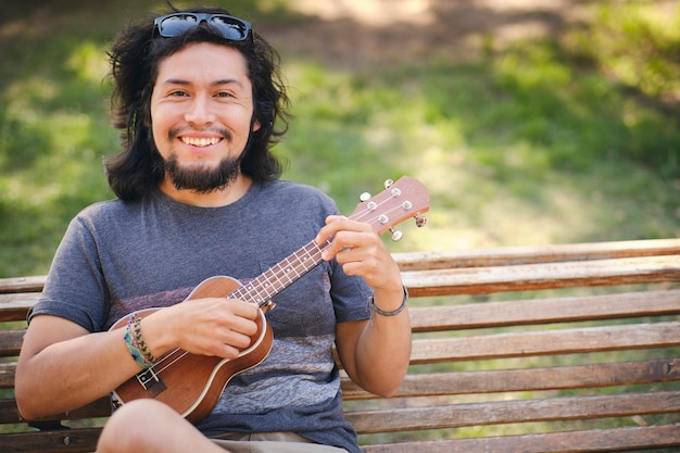 Young man sitting in a park chair playing the ukulele and looking at the camera smile.