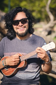 Young man sitting in a park chair playing the ukulele and looking at the camera smile