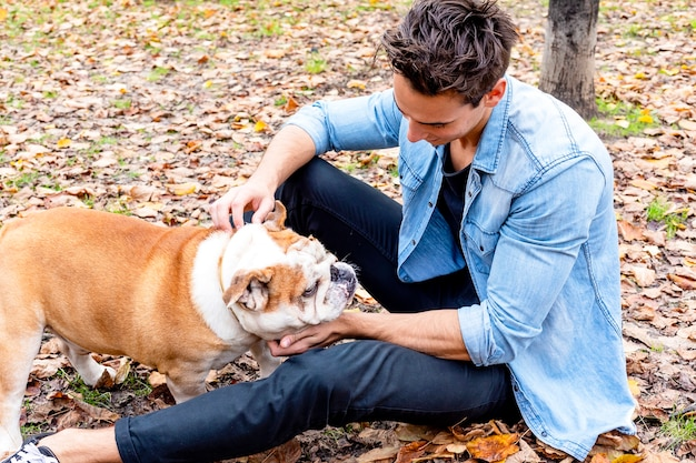 Young man sitting on park ground with his dog