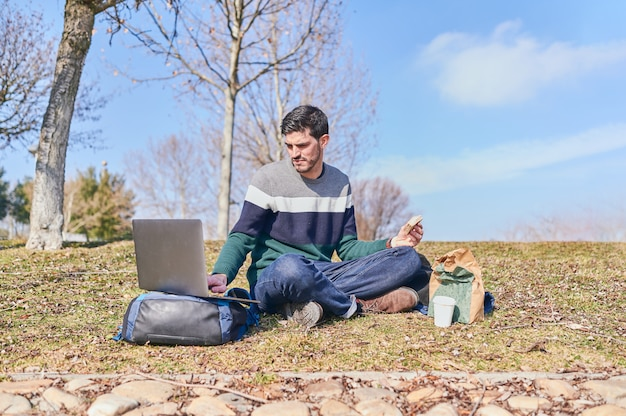 Young man sitting on a park lawn eating a sandwich while working on his laptop