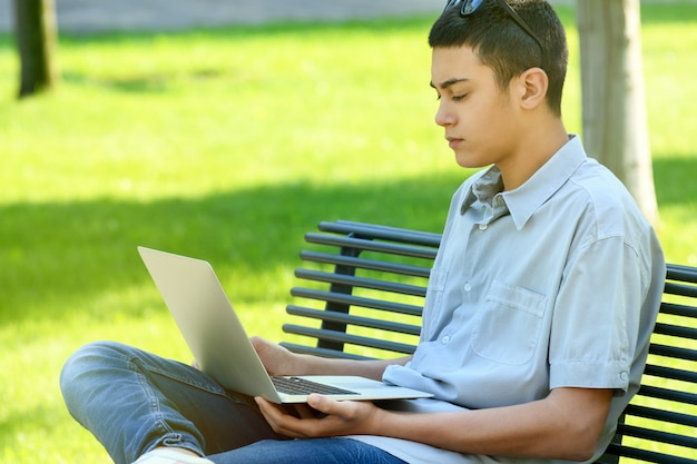 Young man sitting in a park using a laptop