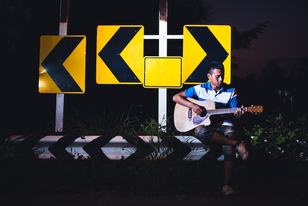 Young man sitting and playing guitar on road side with road sign background, journey of musician concept