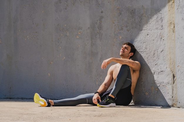Young man sitting resting after training sunbathing without shirt