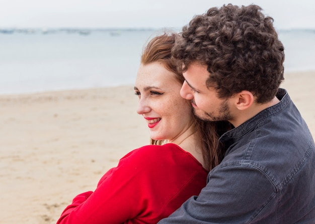 Young man sitting on sea shore and hugging woman