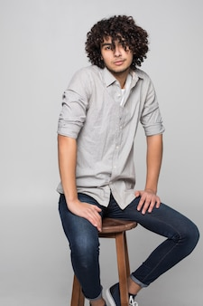 Young man sitting on a small stool against white wall