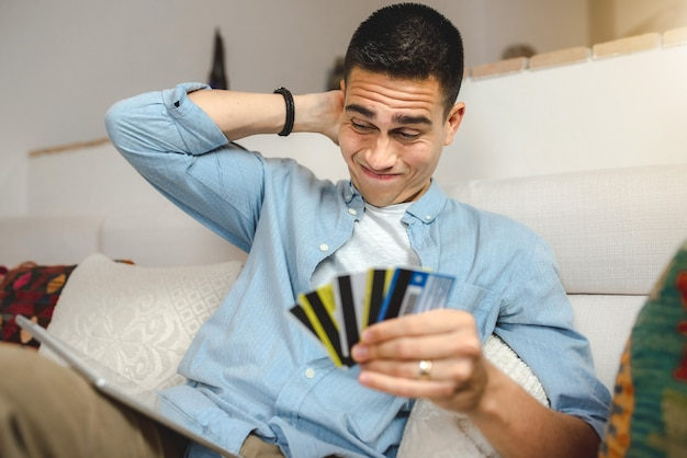 Young man sitting on sofa at home holding tablet and many credit cards.