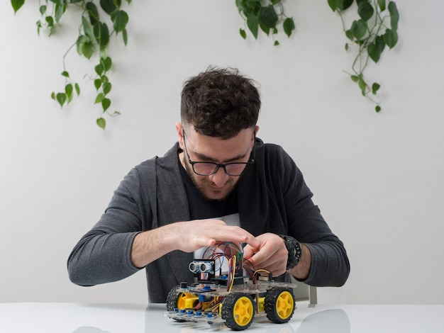 Young man sitting in spectacles watches grey jacket constructing machine toy along with plant on white