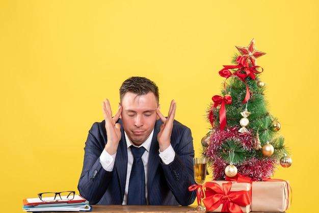 Giovane uomo seduto al tavolo vicino albero di natale e regali su giallo