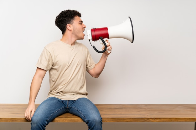 Young man sitting on table shouting through a megaphone