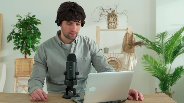 Young man sitting at table with laptop talking on mic