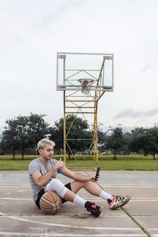 放棄されたバスケットボールコートで自分撮りをして座っている若い男。