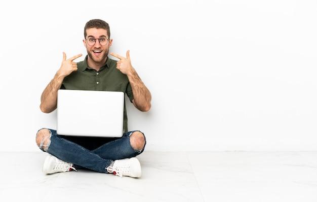 Молодой человек сидит на полу, показывает палец вверх Premium Фотографии