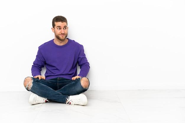 Молодой человек сидит на полу, делая жест сомнения, глядя в сторону