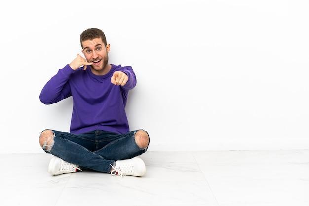 Молодой человек сидит на полу, делая жест телефона и указывая вперед
