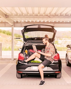 Young man sitting in trunk with laptop