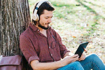 Young man sitting under the tree listening music on headphone through mobile phone