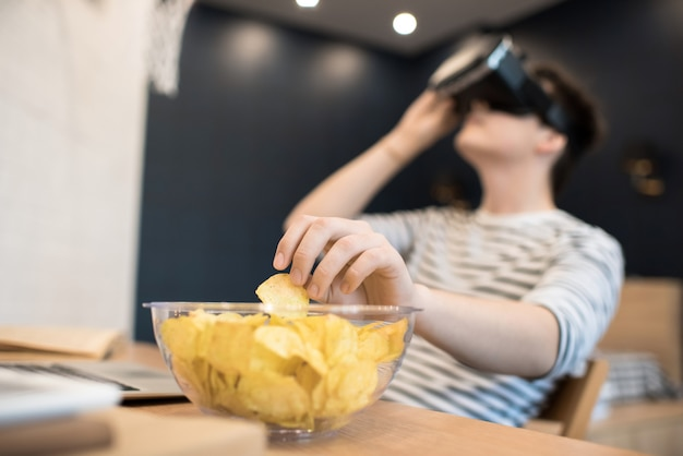 Young man sitting in vr glasses and taking chip