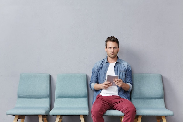 Young man sitting in waiting room holding tablet