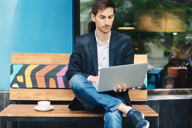 Молодой человек сидит во время работы на ноутбуке